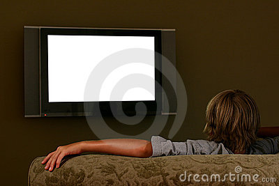 Boy sitting on couch watching widescreen television