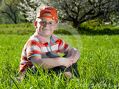 Boy sitting on field of grass
