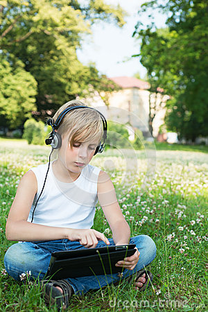 Boy is sitting on the grass in the headphones with your tablet