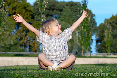 Boy sitting on a grass with the lifted hands