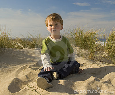 Boy sitting on a grassy dune