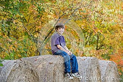Boy Sitting on Hay Bales