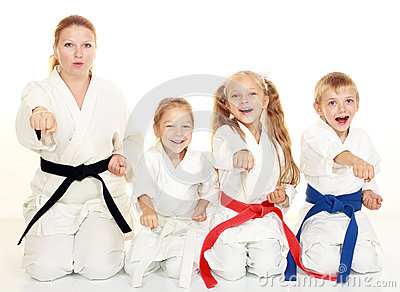 A boy sitting with his sister and mom with her daughter  in a ritual pose karate and beat his fist