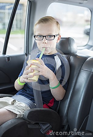 Free Boy Sitting In A Car Seat Drinking A Smoothie On A Long Car Ride Royalty Free Stock Images - 103436529
