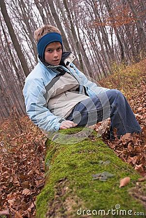 Boy sitting on mossy log