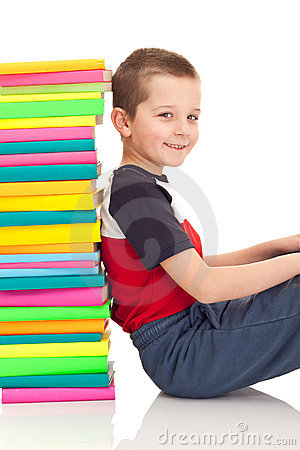 Boy sitting next to stack of books