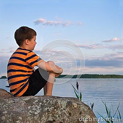 Free Boy Sitting On A Large Rock Watching A Seaside Landscape Stock Photo - 33998550