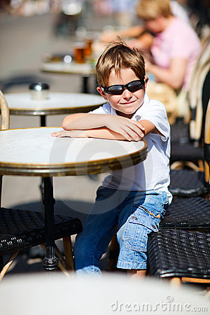 Boy sitting in outdoor cafe