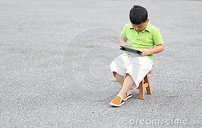 Boy sitting play a tablet