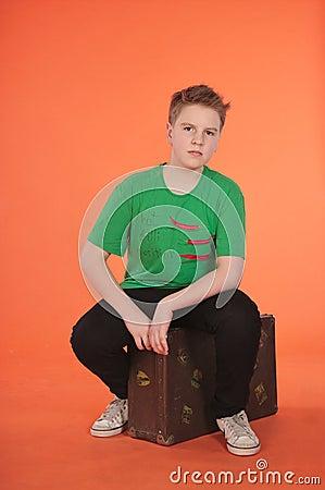 Boy sitting on suitcase