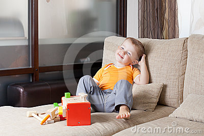 Boy sitting with wooden building toys at home