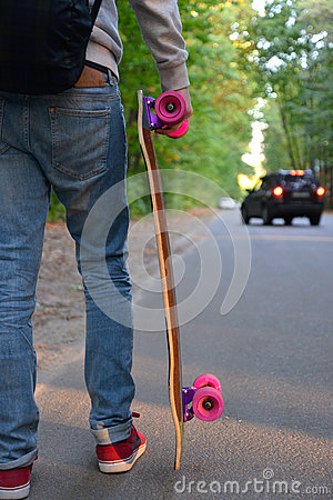 Boy with skateboard on the road