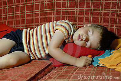 Boy sleeping on a red sofa