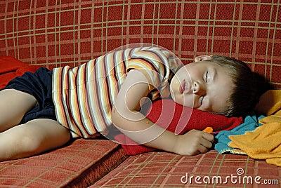 Boy sleeping on a red sofa