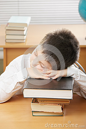 Boy sleeping on stack of books