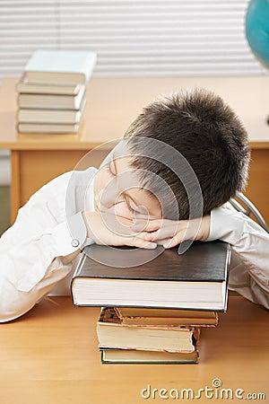 Boy sleeping on stack of books
