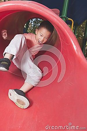 Free Boy Sliding On Playground Stock Image - 62452831
