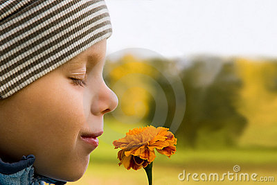 Boy smelling flower
