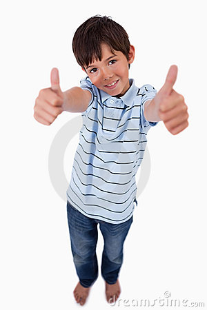 A boy smiling at the camera with the thumbs up