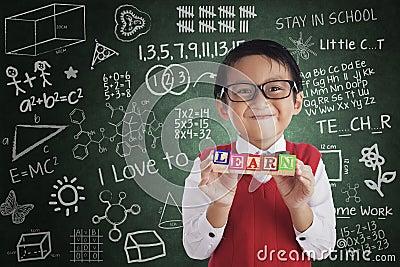 Boy smiling hold learn crossword in class