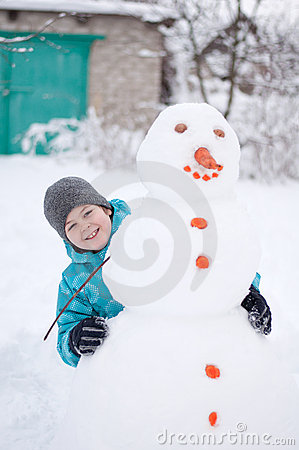 Boy and a snowman - winter holiday