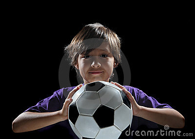Boy with soccer ball on dark background