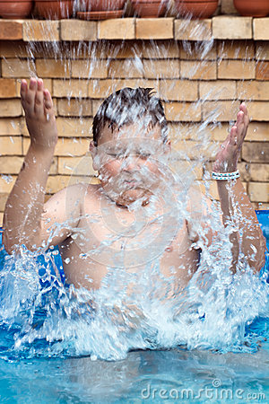 Boy splashes water in swimming pool