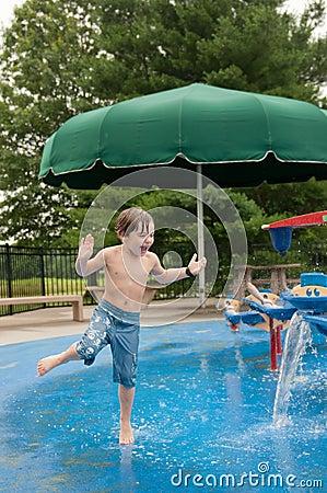 Boy Splashing at Water Spray Park