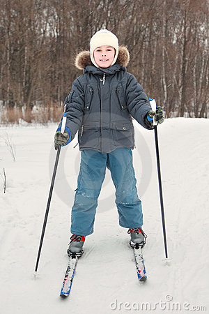 Boy in sport dress skiing at forest