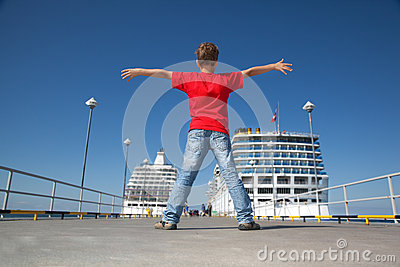 Boy spread hands against background two ships