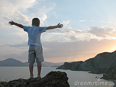 Boy stand on mountain top with hands up
