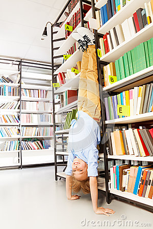 Boy Standing On Arms Upside Down In Library Stock Photo