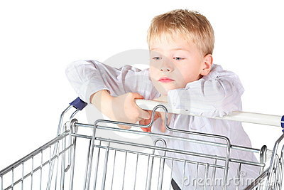 Boy is standing near shoping basket and looking