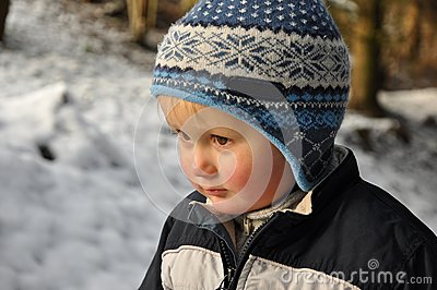 Boy standing in snowy forest