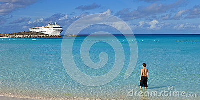Boy standing on tropical beach with cruise ship