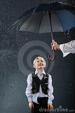 Boy standing under umbrella in rain