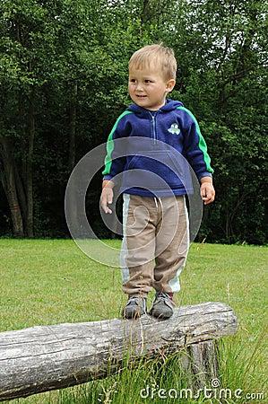 Boy standing on wooden bar