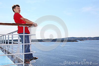 Boy stands on deck of ship and shouts