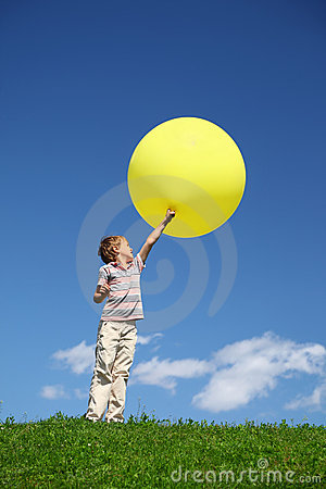 Boy stands in field and lifts balloon