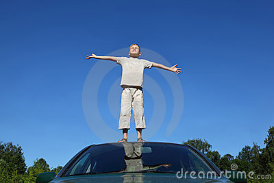 Boy stands on head of auto lifting head to sky