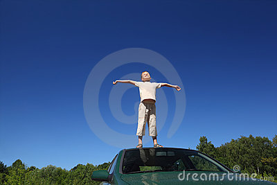 Boy stands on  head of auto, sends hands in sides