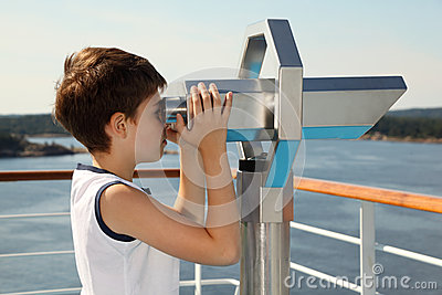Boy stands and looks through binoculars