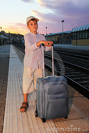 Boy stands on platform of railway with travel bag