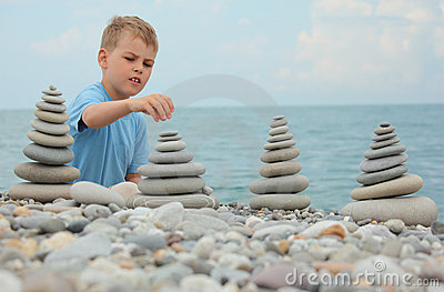 Boy and stone stacks on pebble beach