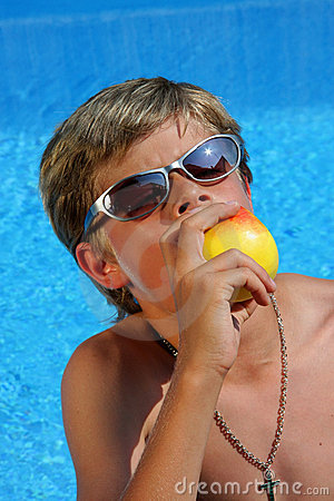 Boy with sun glasses eating an apple with pleasure