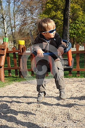 Boy with sunglasses on swing