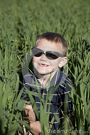 Boy with sunglasses in tall oat field