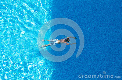 Boy is swimming in a blue pool. Top view