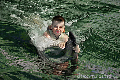 Boy swimming with dolphin closeup
