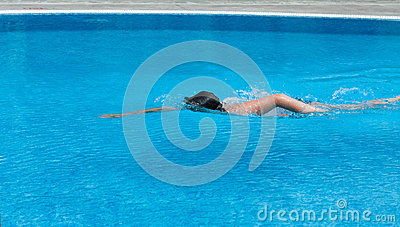 A boy is swimming in a pool. Side view